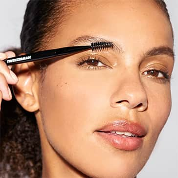 Woman grooming her brows with the new Tweezerman Brow & Lash Brush